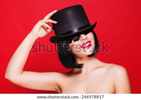 fashion model in hat cylinder, on red background - stock photo