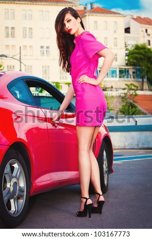 fashion model in pink dress and high heels stand by the red car - stock photo