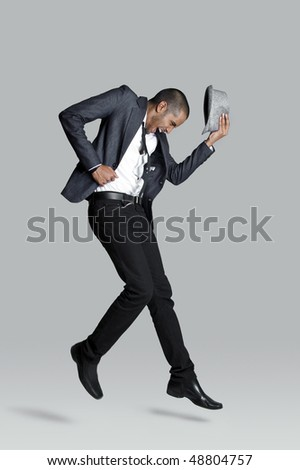 Fashion model jumps and has happy expression in studio - stock photo