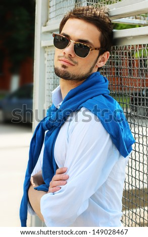 Fashion model macho male front fence outdoor - stock photo