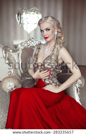 Fashion model portrait of beautiful sensual blond woman with makeup in luxurious dress with bijou, posing on modern armchair with sliver frames. Indoor photo  - stock photo