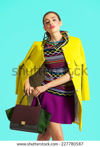 Fashion model pose on light blue background in yellow clothes - stock photo
