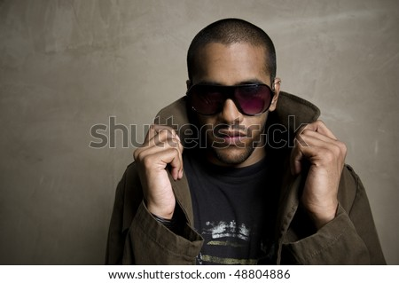 Fashion model poses in front of a grunge wall - stock photo