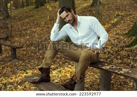 Fashion model posing in autumn scenery - stock photo