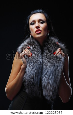 Fashion model posing in studio covering her neck in a fur - stock photo