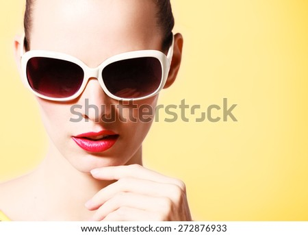 Fashion model striking a pose wearing sunglasses. - stock photo