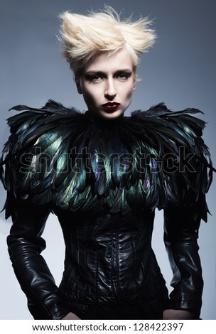 fashion model wearing a costume made of leather and feathers posing on blue background - stock photo