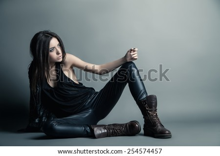Fashion model wearing leather pants and jacket posing on grey background - stock photo
