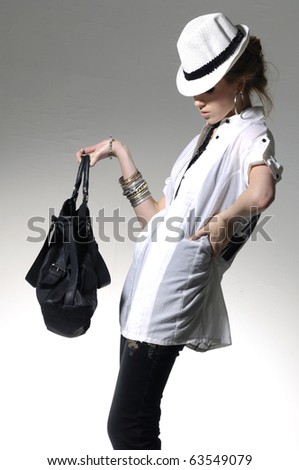 Fashion model wearing the big modern sunglasses with bag - stock photo