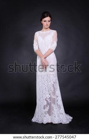 Fashion model wearing wedding dress at black studio background - stock photo