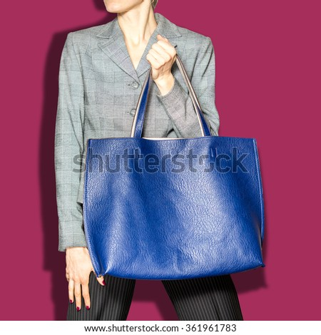 Fashion model with bag over plum background. posing in the studio - stock photo