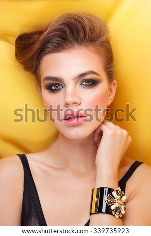 Fashion model with jewelry, modern evening make up. Silk yellow background. - stock photo