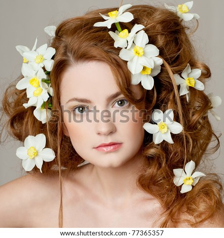 fashion model with large hairstyle and flowers in her hair. - stock photo