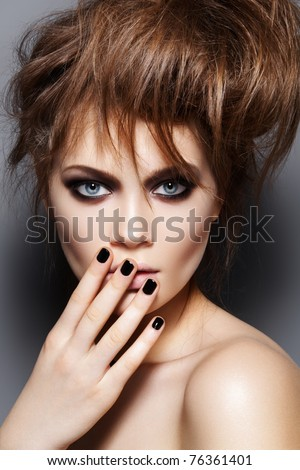 Fashion model with tousled hair, make-up, manicure. Portrait of young fashion woman with punk rock hairstyle, dark make-up, black nail polish - stock photo
