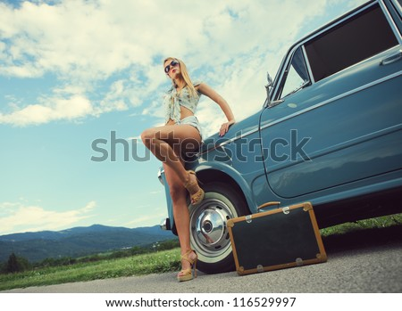 Fashion model with vintage cars, cloudy sky on background - stock photo