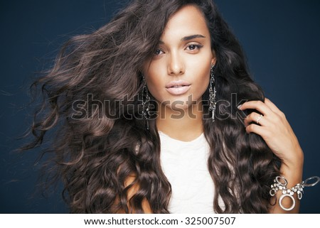 Fashion model with wavy hairstyle. portrait of young woman with makeup and healthy skin. Toned in warm colors. Studio shot, horizontal - stock photo
