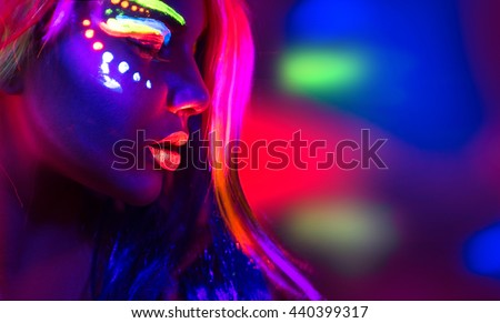 Fashion model woman in neon light, portrait of beautiful model girl with fluorescent make-up, Body Art design of female disco dancer posing in UV, painted face, colorful make up, over black background - stock photo