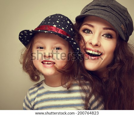 Fashion mother and kid girl happy toothy laughing in trendy caps. Vintage closeup portrait - stock photo