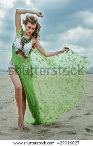 Fashion outdoor photo of beautiful sexy woman with blond hair wearing luxury design bikini and holding fluttering cover up on the beach. - stock photo