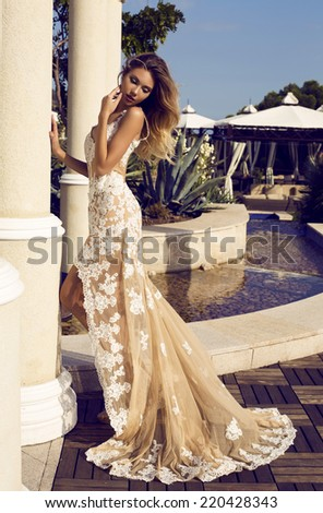 fashion outdoor photo of beautiful woman with blond hair in elegant luxurious dress posing beside a column at park - stock photo