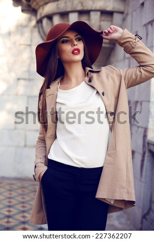 fashion outdoor photo of beautiful woman with dark straight hair and bright makeup,wearing elegant clothes and posing in autumn park - stock photo