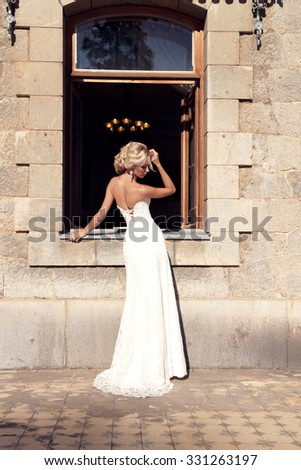 fashion outdoor photo of gorgeous bride with blond hair wears luxurious dress and accessories,posing in antic villa  - stock photo