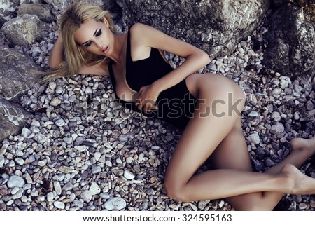 fashion outdoor photo of gorgeous sexy woman with blond hair in elegant bikini relaxing on summer beach  - stock photo