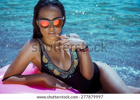 fashion outdoor photo of sexy beautiful woman with long hair in elegant black bikini with accessories relaxing on summer beach. horizontal shot - stock photo