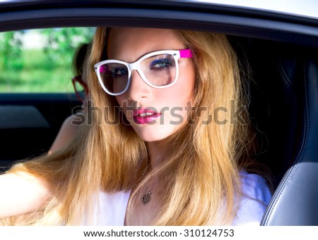 Fashion outdoor portrait of beautiful woman with blonde hair in white t-shirt and clear sunglasses sitting on driver seat in luxurious auto.Hipster Woman driving sportive Car On Road Trip - stock photo