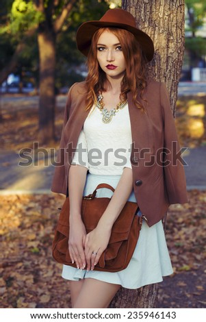 fashion outdoor portrait of cute young redhead woman in beige hat and jacket with beautiful necklace and curly hair holding a red bag and standing near the tree in the citi park  - stock photo