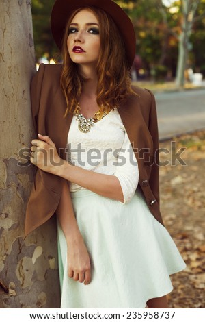 fashion outdoor portrait of cute young redhead woman in beige hat and jacket with beautiful necklace and curly hair and standing near the tree in the citi park  - stock photo