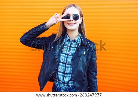 Fashion outdoor portrait of pretty cool girl in trendy rock style having fun against a colorful orange urban wall - stock photo