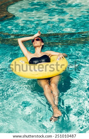 Fashion outdoor portrait of pretty sexy brunette tanned woman having fun in summer on tropic island close to swimming pool with clear deep blue water Full relax vintage and happiness - stock photo