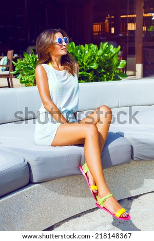 Fashion outdoor portrait of pretty tan sportive woman relaxed and enjoy sunny hot day at her vacation on luxury resort, wearing casual beach dress and sunglasses. Bright sunny colors. - stock photo