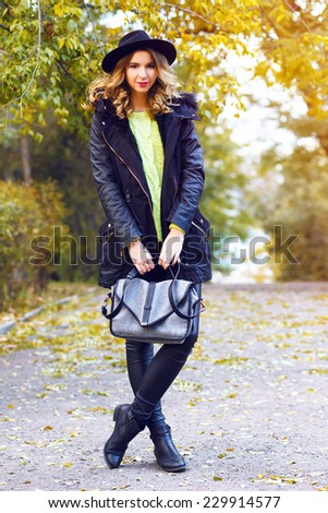Fashion outdoor portrait of stylish woman wearing black leather outfit, neon sweater and retro hat. Street style look. Amazing background of beautiful fall autumn golden leaves. - stock photo