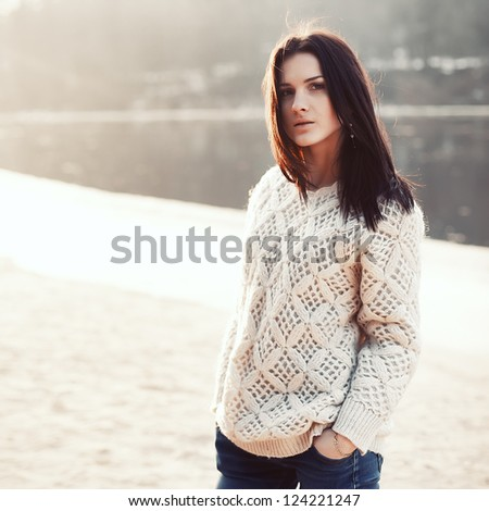 Fashion outdoor portrait of young beautiful brunette. Girl posing on the beach. Sunny soft warm colors. - stock photo
