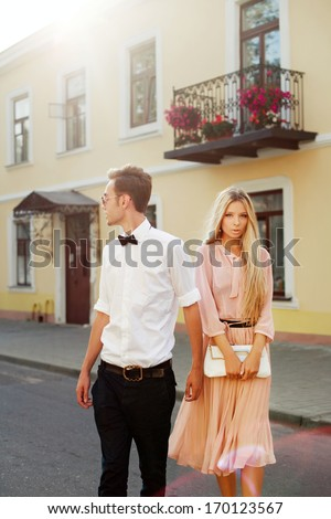 Fashion outdoor portrait of young fashion couple in love walking on the street and having fun together - stock photo