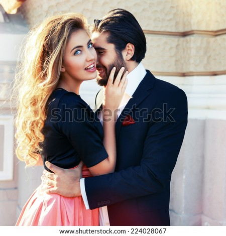 Fashion outdoor portrait of young sensual couple posing near theater in elegant classic clothes, fashion suit and dress, hugs and kissing on the street at evening sunlight. - stock photo