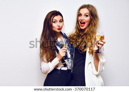 Fashion party portrait of elegant funny sister girls having fun laughing and gossip, ready for celebration drinking champagne, black and white glamour party,bright makeup , joy, emotions, cheers. - stock photo
