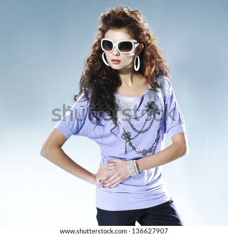 Fashion photo, a model is posing over light background - stock photo