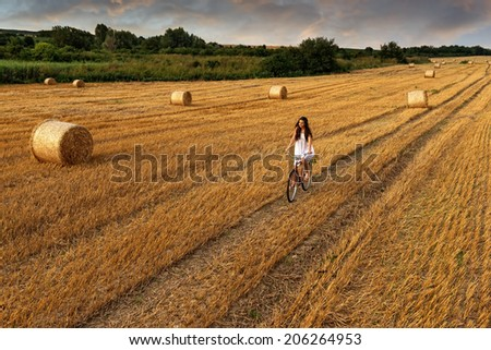 Fashion photo, beautiful woman cycling in a wheat field, a lot of bales of wheat  - stock photo