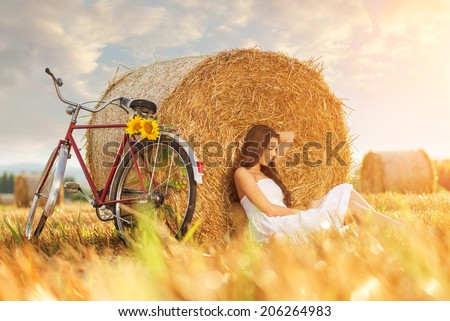 Fashion photo, beautiful woman sitting in front of bales of wheat, next to the old bike  - stock photo
