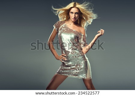 Fashion photo of a stunning blonde woman in luxurious glitter dress. - stock photo
