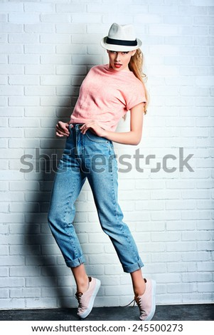 Fashion photo of an attractive young woman posing at studio. Casual, jeans style. Beauty, fashion. Full length portrait. - stock photo