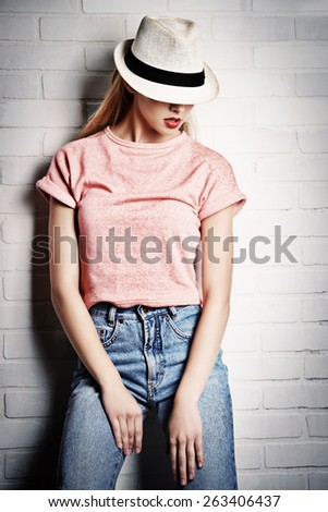 Fashion photo of an attractive young woman posing at studio. Casual, jeans style. Beauty, fashion. - stock photo