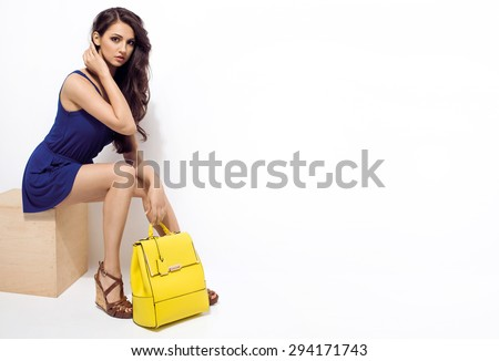 Fashion photo of beautiful brunette woman in blue summer jumpsuit, yellow backpack, wedges shoes. Shopping mall. Sales and discounts concept - stock photo