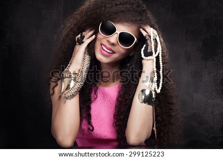Fashion photo of beautiful elegant african american woman. Girl posing with a lot of jewelry, wearing fashionable sunglasses, smiling. Girl with long curly healthy hair. Beauty portrait. Studio shot. - stock photo