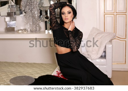 fashion photo of beautiful gorgeous woman with dark hair in elegant dress,posing in luxurious interior - stock photo