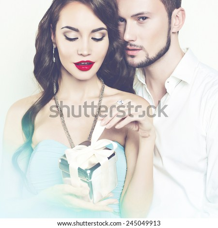 Fashion photo of beautiful romantic couple with gift - stock photo