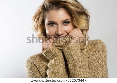 Fashion photo of beautiful woman in sweater. Curly hairstyle. Make-up. - stock photo